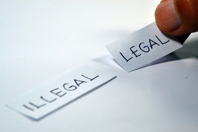 hand picking a piece of paper with the word legal