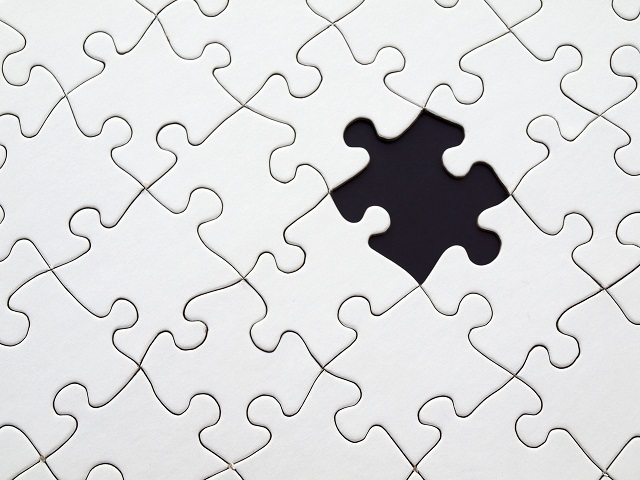 white puzzle with a black piece fitting inside